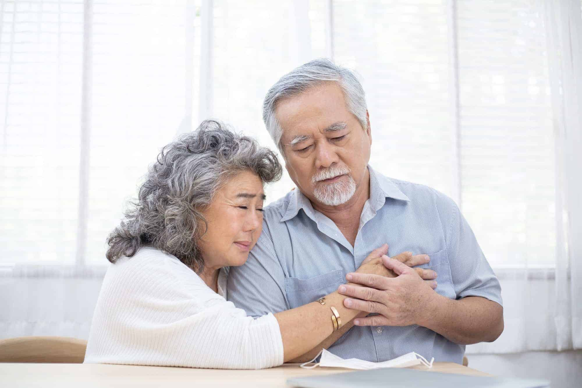 Asian wife embrace senior husband after receive diagnosis of sickness