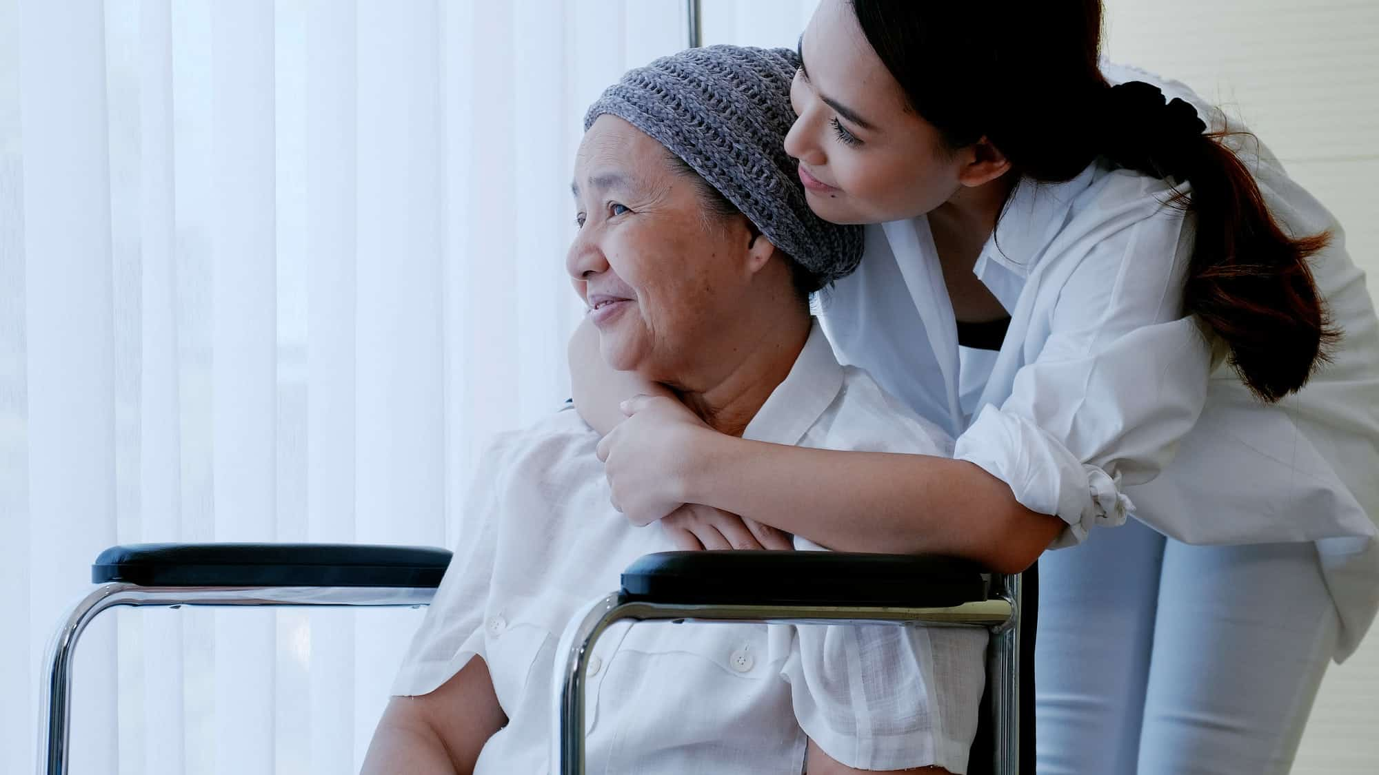 daughter encourages and comforts a mother with cancer during hospitalization.
