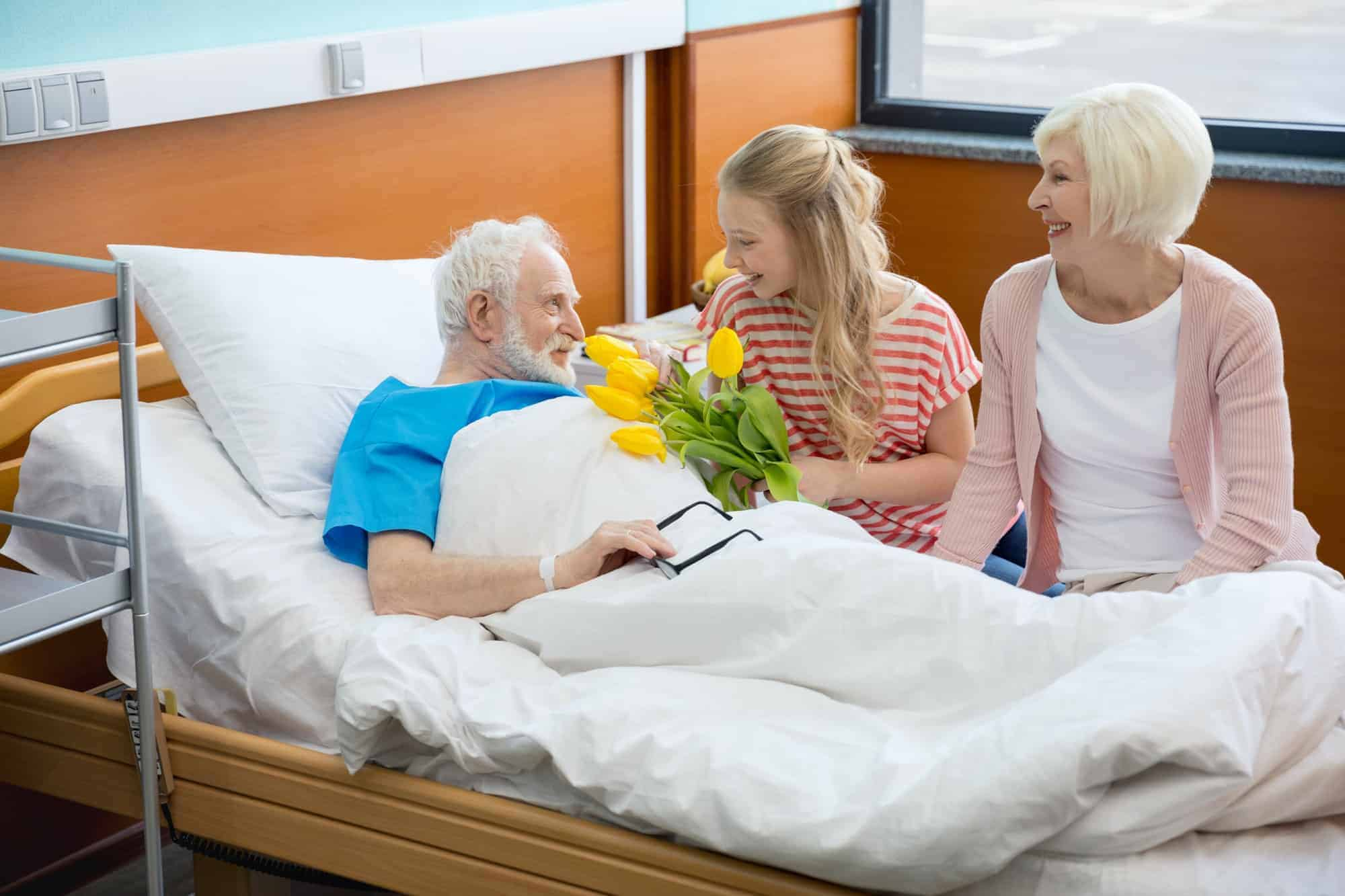 grandmother and granddaughter with tulip flowers visiting patient in hospital. male patient in