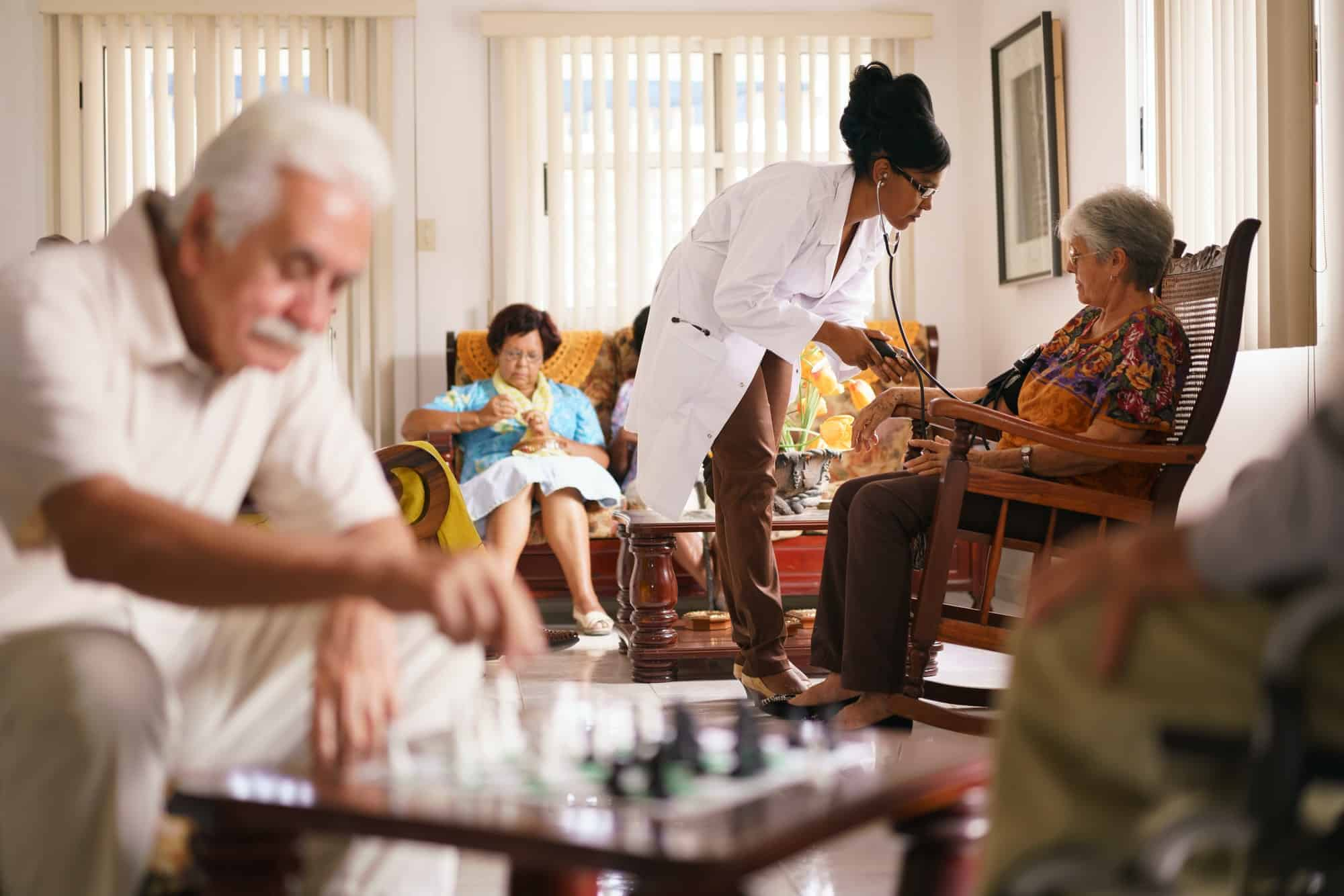 Hospice Doctor Measuring Blood Pressure To Senior Woman