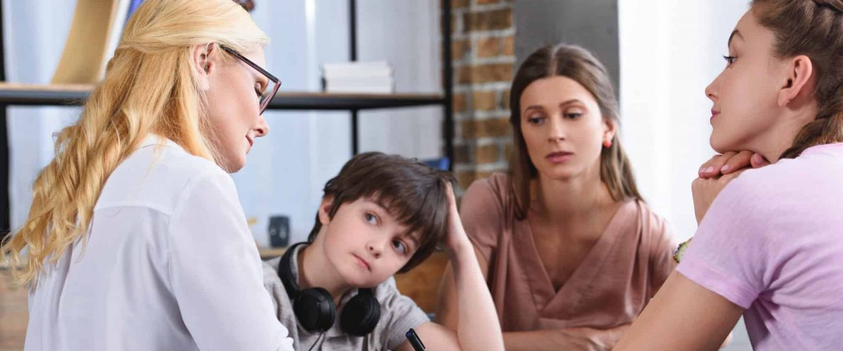 female counselor writing in clipboard on therapy session with family in office