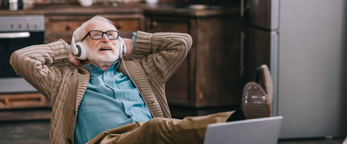 Happy old man in headphones using laptop with feet on table