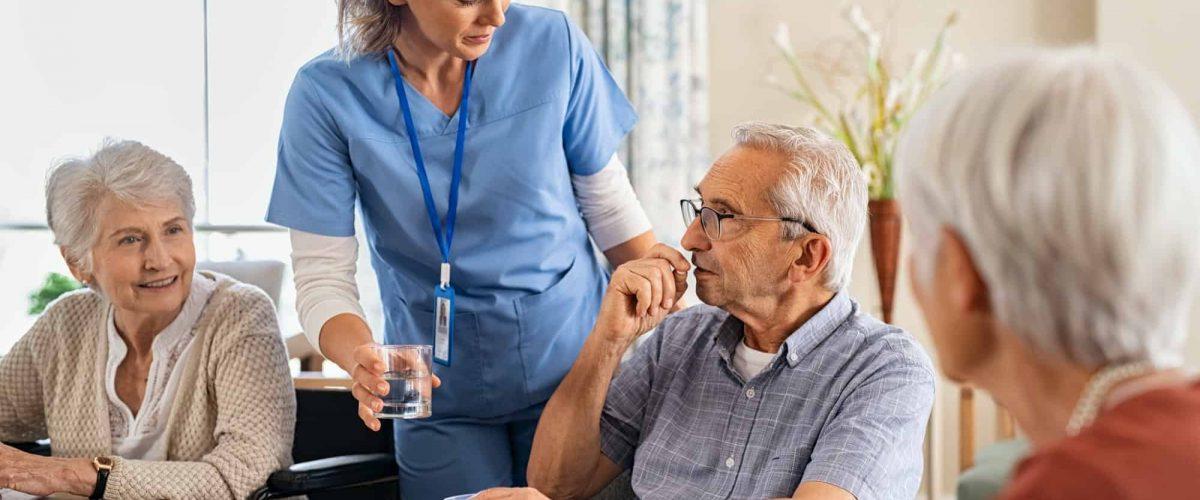 Nurse helping senior man to take his daily medicine at hospice