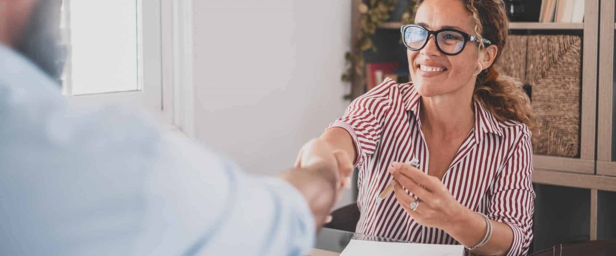 Smiling caucasian female hr manager handshake hire male candidate at job interview