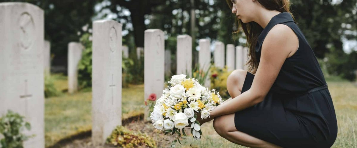 Young widow laying flowers at the grave